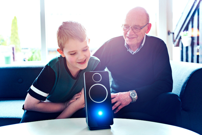 A boy sits in a sofa with his grandfather and they are bonding with help of consumer electronics. In front of them on a table stand a digital assistant, which is an intelligent loudspeaker with built-in microphone. The digital assistant can help answer questions and enable the family to control internet of things such as lightbulbs and door locks with voice commands.