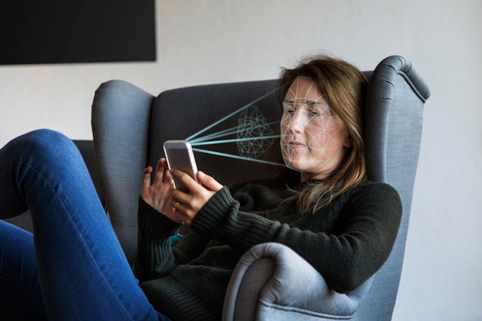 Young woman holding her smartphone up to her face to verify her identity (ID) with biometric facial recognition software. Facial recognition is a system whereby a user's face is scanned to verify his or her identity.
